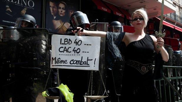 """Una manifestante sostiene una balanza y una pancarta que dice """"LBD40, CAC40 la misma lucha"""" frente a la policía antidisturbios francesa durante una manifestación (Reuters)"""