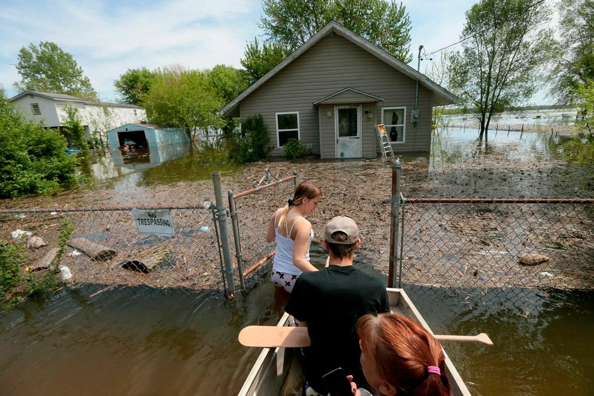 Una familia intenta ingresar a su casa en medio de las inundaciones en East Foley, Misuri, el 5 de mayo de 2019. (AP)