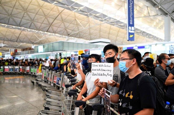 Los manifestantes traban el paso delos pasajeros en los pasillos de salida del aeropuerto de Hong Kong, un día después de que una sentada obligara a las autoridades a cancelar todos los vuelos hacia y desde la terminal(Foto de Manan VATSYAYANA / AFP)