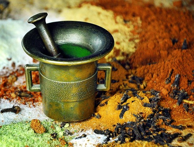 Mortar and pestle with Turmeric and spices. Golden milk for joints.