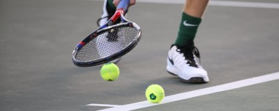 A person dribbling tennis balls on a court with their racket