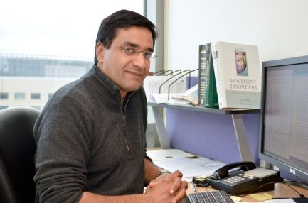 Vivek Unni, M.D., Ph.D., sitting at his desk