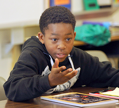 photo of student speaking at his desk