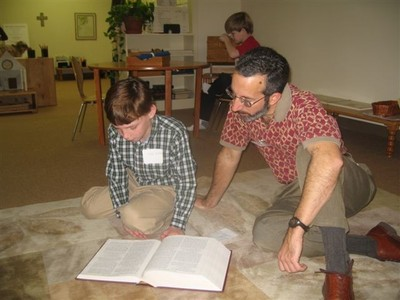 Tom and child reading book on floor
