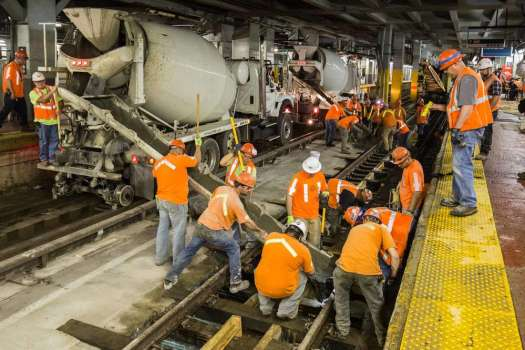 Amtrak photo Amtrak crews pour concrete onto track 7 of New York Penn Station, in order to hold wooden ties in place that support rails that carry approximately 1,300 weekday train movements for three different railroads.