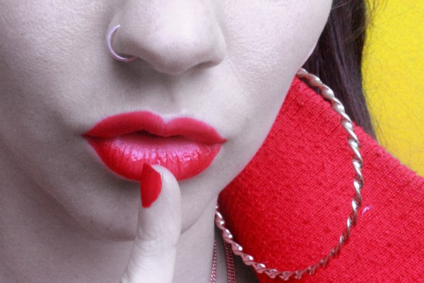 Confession - a girl with red lipsticks pits her finger to her mouth, indicating be quiet
