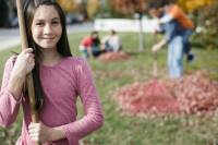 A girl holding a leaf rake and people raking fallen autumn leaves into piles.