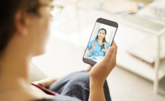 Doctor talking to a patient on a mobile phone during telemedicine video call