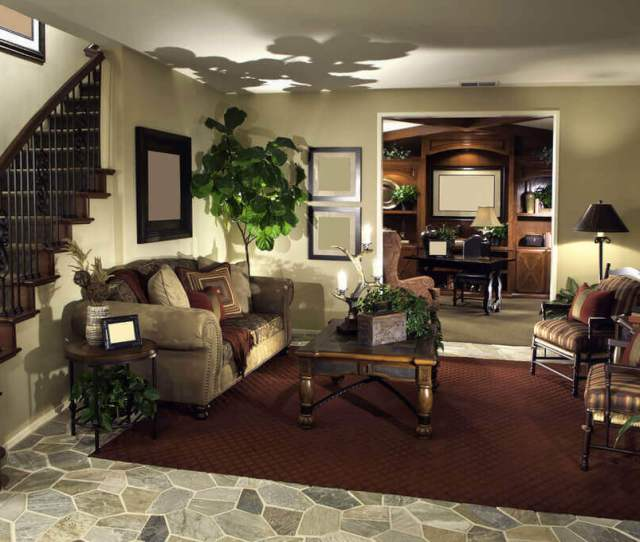 This Cozy Living Room Setup Stands Beneath The Carved Wood And Wrought Iron Stair Railing At