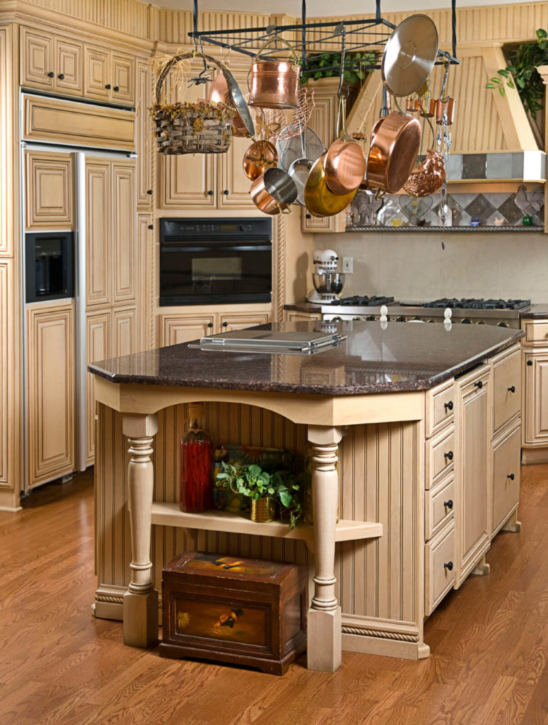 This beautiful kitchen is reminiscent of ancient architecture. The lovely floor complements the color choices and balances the light stained wood paneling.
