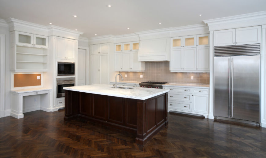 The broad herringbone dark wood floor of this kitchen makes for a detailed base in a bright and bold white room. The large island features a built-in sink and is topped with rich white marble.