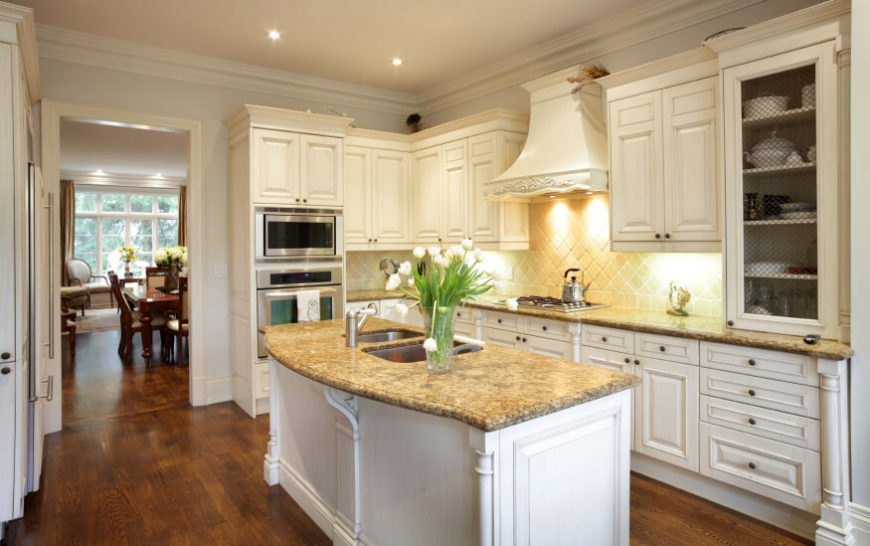 Discreet under-cabinet lighting adds a flash to the white cabinetry and tile backsplash in this kitchen. A large island stands over hardwood flooring with beige granite countertop.