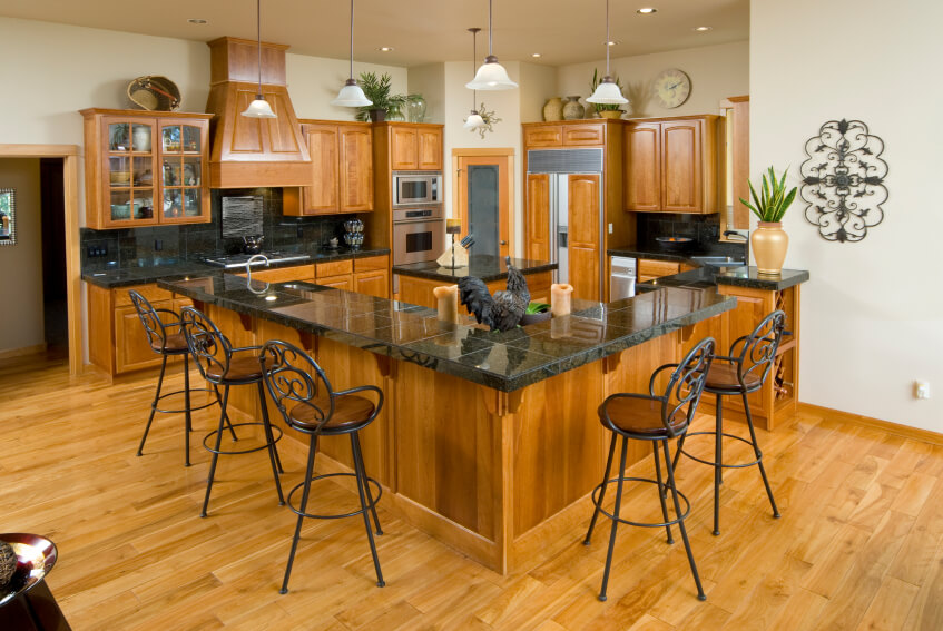The bright wood of this kitchen help to keep the dark countertops from becoming overbearing in this space.