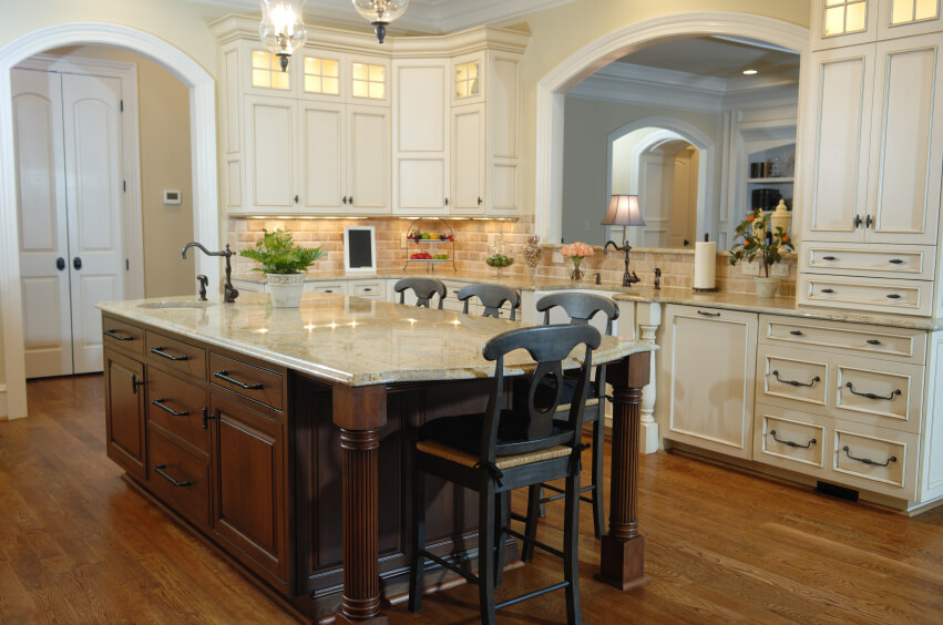 This luxuriously appointed kitchen features an extra layer of contrast, with both rich hardwood flooring and darker stained wood island competing against white cabinetry. The backsplash is a layer of tan brick tile, while the massive island is topped by beige marble.