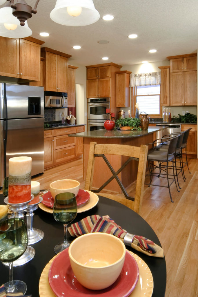 The warm wood in this kitchen enhances the accent colors chosen. The use of full height cabinetry unifies the tone of the room.