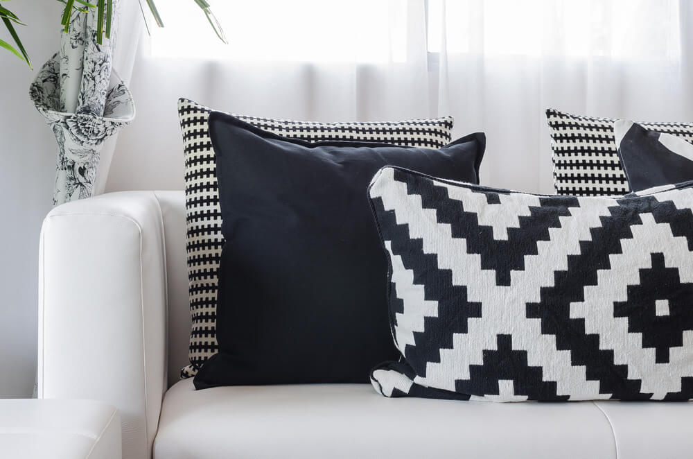 White sofa with black and white pillows. Striking effect. Pillows include solid and geometric patterns.