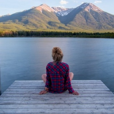 A woman sat in from of a lake. - the best mindfulness book