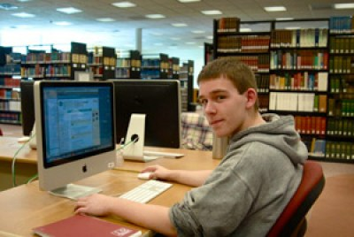 A Potsdam student works on a computer in the Makerspace