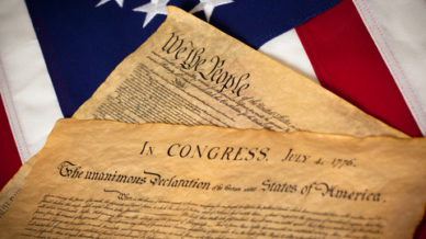 dreamstime_xs_23487952_CONSTITUTION & DECLARATION OF INDEPENDENCE ON FLAG by Miflippo