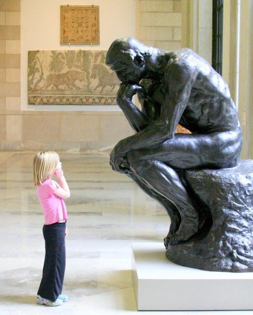 Estatua pensando y niña mirandola