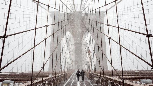 Peatones se protegen de la nieve y del viento mientras cruzan el puente de Brooklyn durante una tormenta de viento y nieve en Nueva York (Estados Unidos). EFE