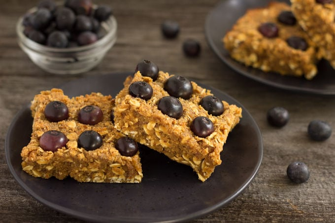 These homemade blueberry protein bars are soft, chewy and moist. Ready in about 20 minutes, these delicious healthy bars are easy to prepare and only require one bowl and your hands to whip up. Perfect either as a post-workout snack or simply as a dessert, they are naturally sweetened, gluten-free, vegan and flourless!