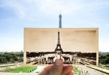 A hand holding an antique photograph of the Eiffel Tower in front of the Eiffel Tower, showing prevalence of pictures in heavily-photographed places