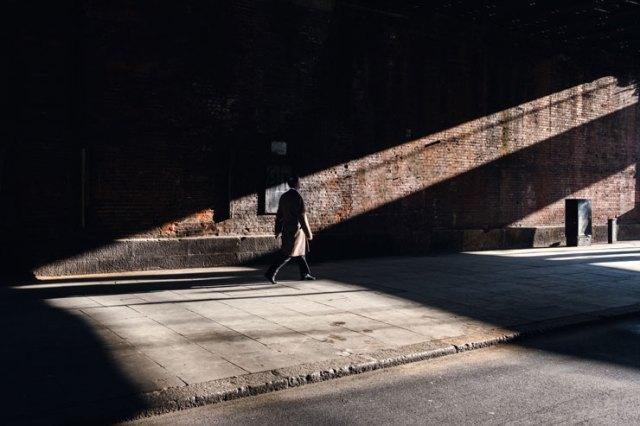 A man walking in a beam of light in London, UK