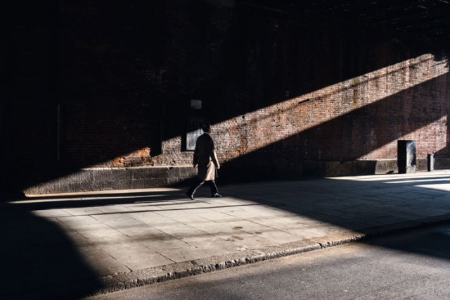 A man walking in a beam of light in London, UK
