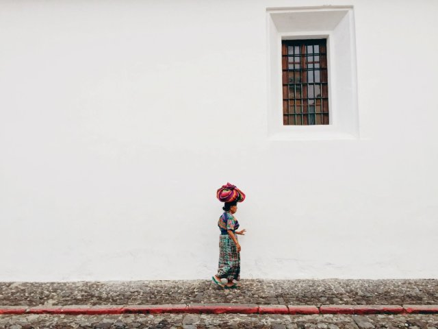 A Latin American woman carrying a colorful bundle on her head