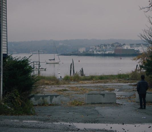 A man looks out toward the waterfront in Gloucester, Massachusetts
