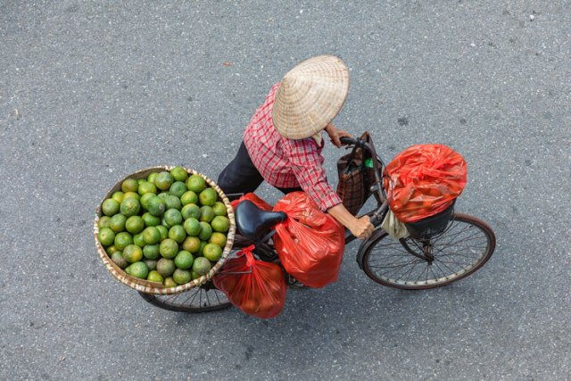 A street vendor in Hanoi walking a bike with a basket of limes
