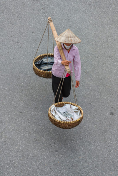 A street vendor in Hanoi carrying baskets of newspaper