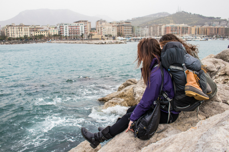 Two backpacking women rest in Salerno.
