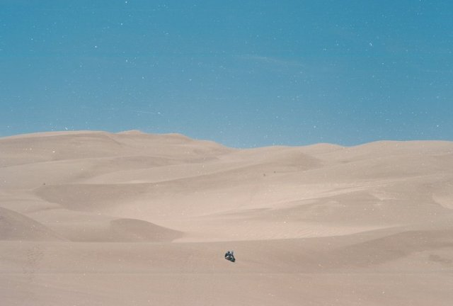 A film photograph of two people sitting in the desert