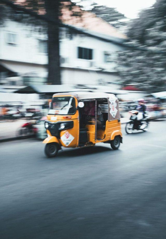 A yellow tuk tuk driving along a street in Cambodia