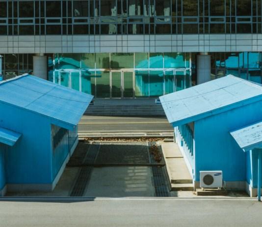 Three guards stand before the Demilitarized Zone (DMZ) in North Korea
