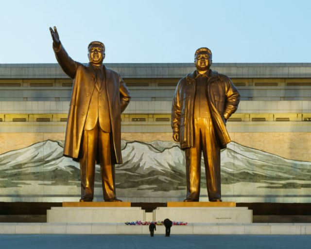 Two people bow before the bronze statues of Kim Il Sung and Kim Jong Il