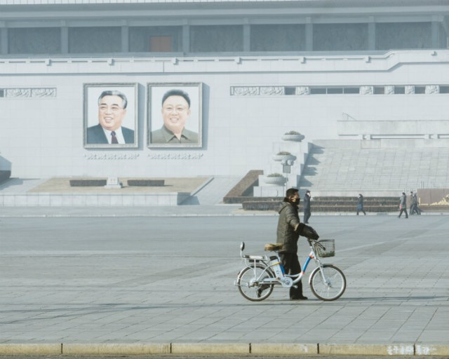 A cyclist in front of the portraits of Kim Il Sung and Kim Jong Il in Pyongyang, North Korea