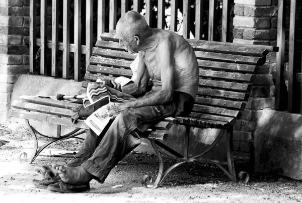 An old man sits on a bench in Venice