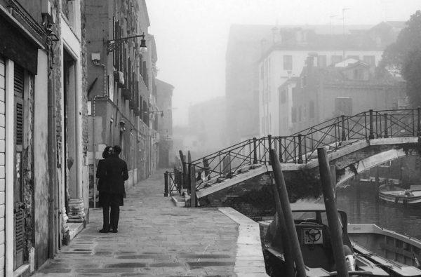 Lovers kiss by a bridge in Venice