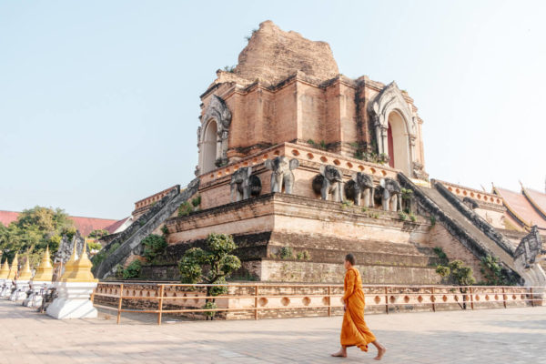 A monk in saffron-colored robes walks before a temple in Chiang Mai, in a photo by creative Denis Amirtharaj.