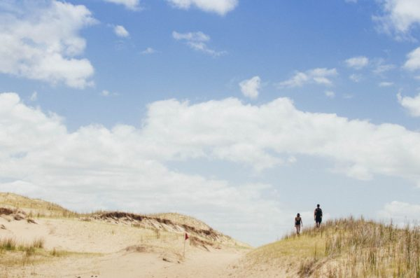A couple walking along the sand dunes in Cabo Polonio, Uruguay