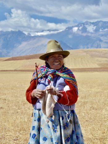 A Peruvian woman knitting in an open field