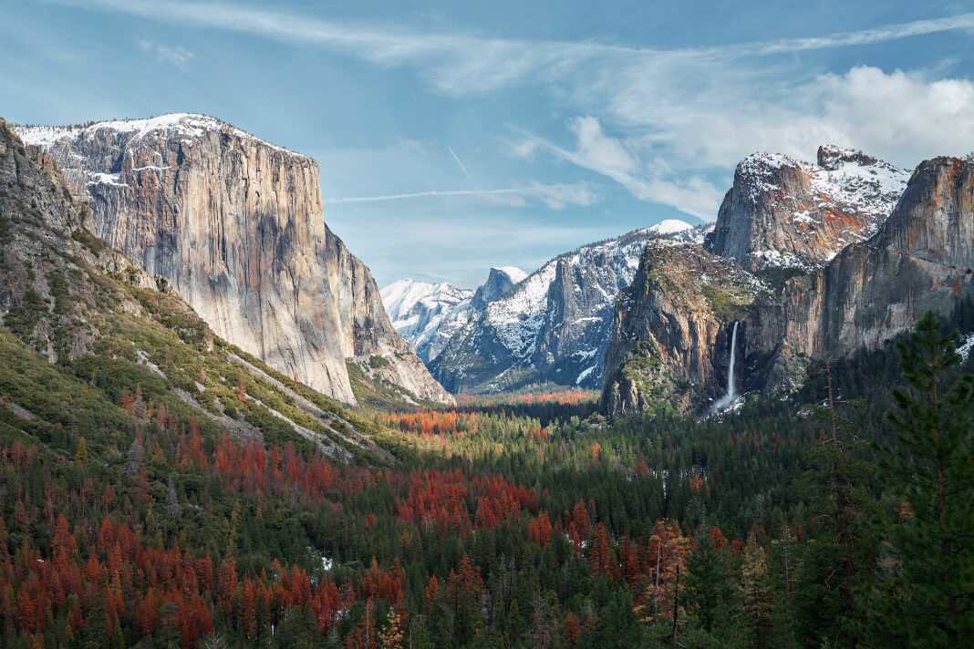 Sea of forest before snow capped mountains in Yosemite Valley, United States