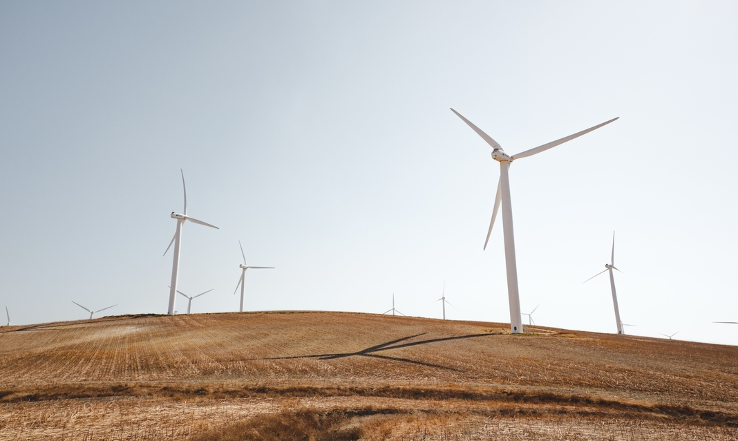 White windmills on a grassy hill against a blue-white sky.