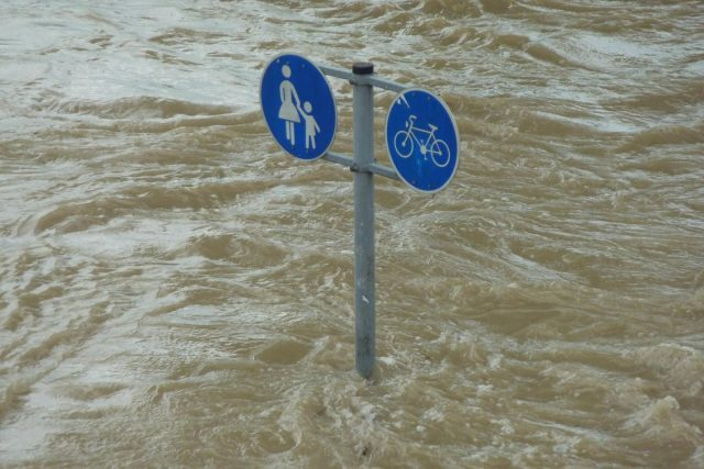 High water levels from flooding and climate change reach up to street signs.