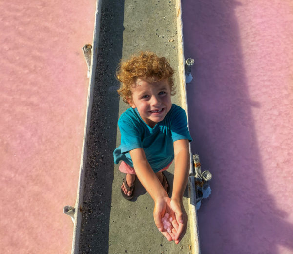 A young boy holds pink salt crystals at the flats in Puerto Rico