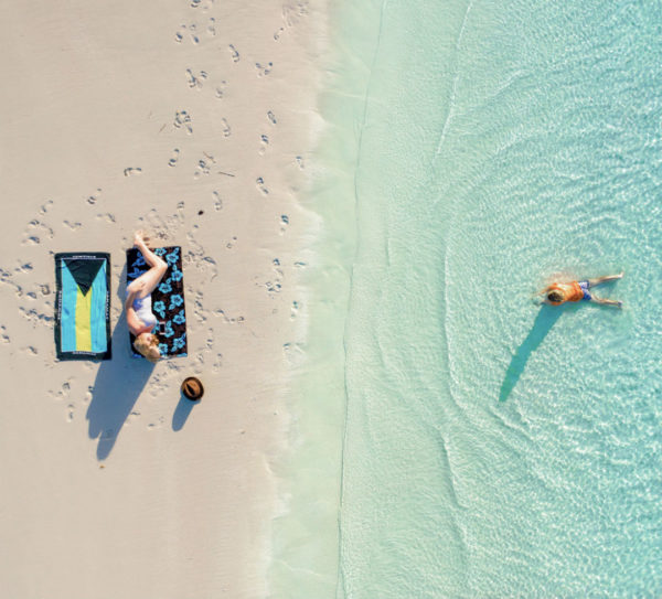 An aerial shot of a pristine beach with a woman tanning and a boy swimming