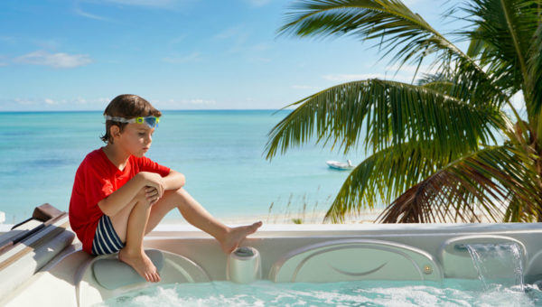 A hesitant young boy dips his toes in a hot tub